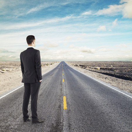 horizont: young businessman standing on road looking to horizont Stock Photo