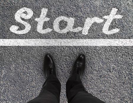 first step: Paar F��e auf einer Asphaltstra�e mit gelbem Aufdruck des Wortes Start