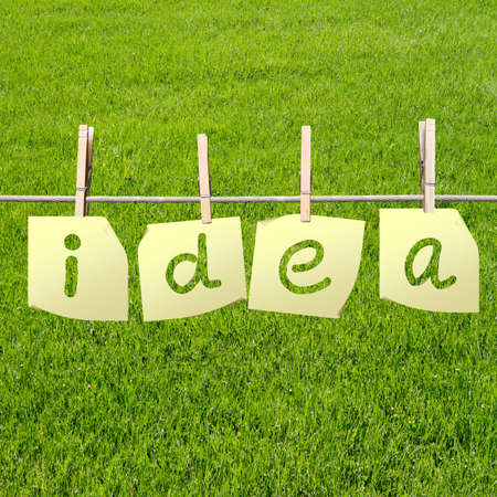 idea word written on sheets of paper on field background photo