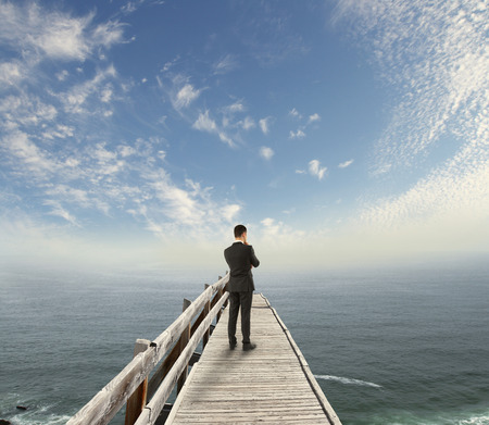 businessman standing: businessman standing on wooden pier and looking to sky Stock Photo