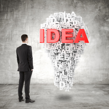 idea symbol: young businessman in suit looking to idea symbol