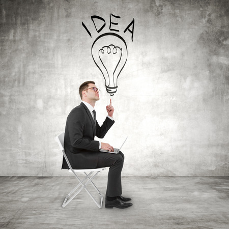 businessman sitting with notebook and pointing to lamp photo