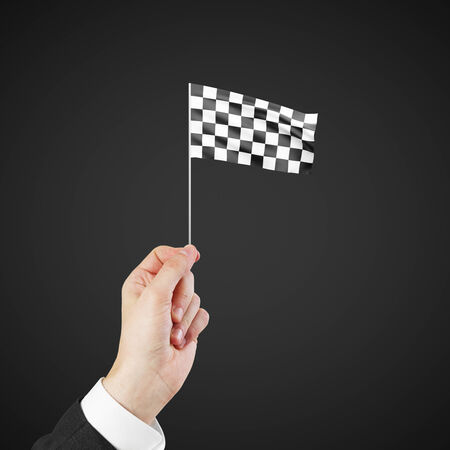 Checkered flag in hand isolated on white background photo