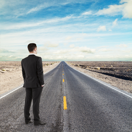 businessman standing on road looking to horizont photo