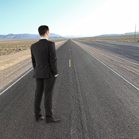 young man standing on road looking to horizont photo