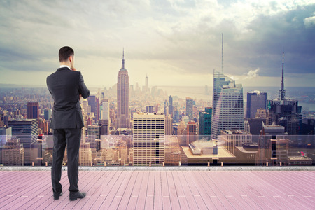 businessman standing on roof and looking at new york Stock Photo