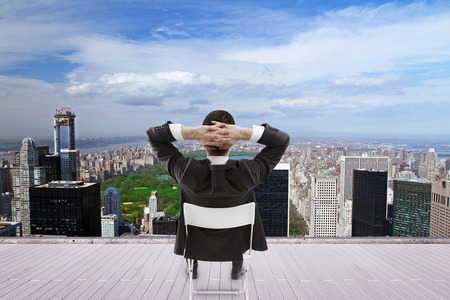 man sitting on roof and looking at city photo