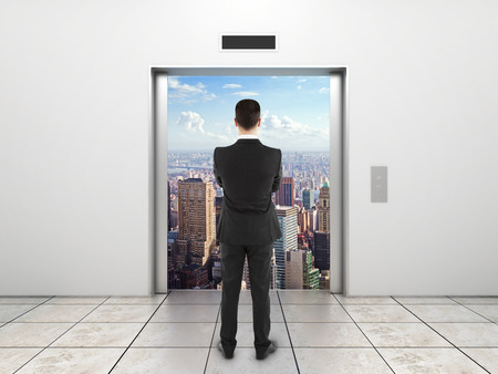 businessman  looking at modern elevator with opened door to city photo