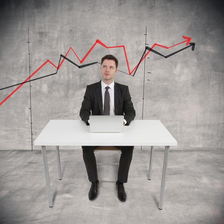 businessman sitting with laptop and drawing chart on wall photo
