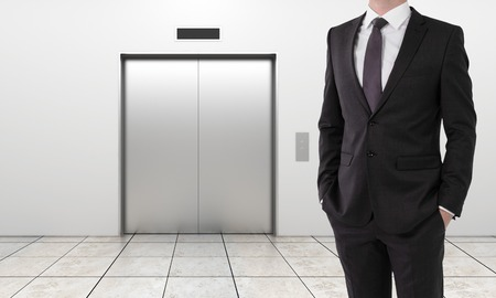 businessman and modern elevator with closed doors photo