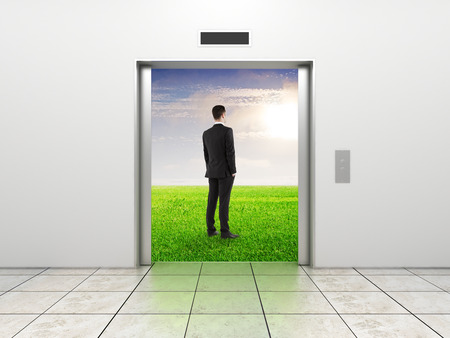 businessman and modern elevator with opened doors to field photo