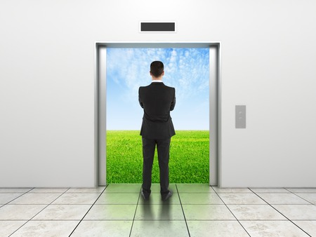 man and modern elevator with opened doors to field photo