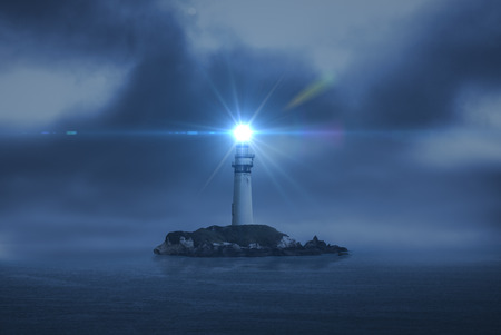 lighthouse searchlight beam through marine air at night Stok Fotoğraf