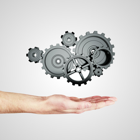 rack wheel: hand holding metal gears and cogwheels on gray background Stock Photo