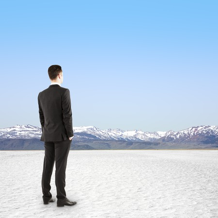 businessman standing in desert landscape with a blue cloudy sky