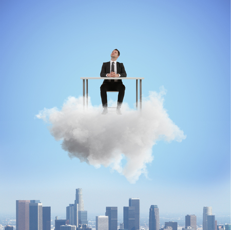businessman sitting at desk on a cloud Stock Photo