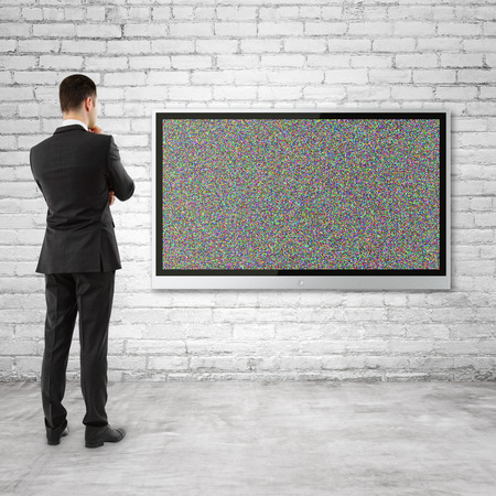businessman looking  to plasma panel with noise on wall