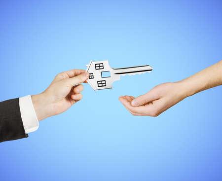 traslados: mano transfiere la llave en forma de casa aislada en azul