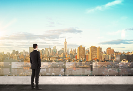 man standing on roof and looking at modern city