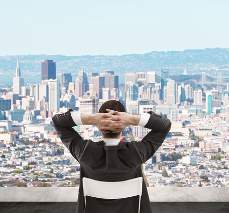 man sitting on roof and looking at modern city photo