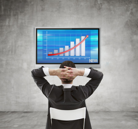 businessman sitting and looking at plasma panel with chart photo