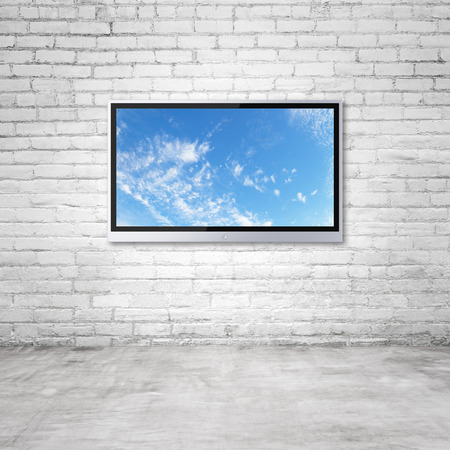 lcd display: wide screen TV with sky on brick wall in room