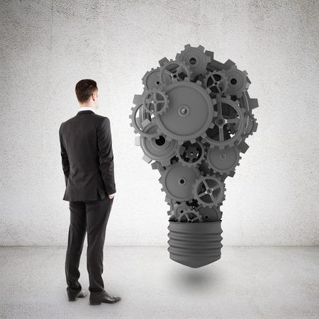 rack wheel: businessman in suit looking at metal gears in concrete room