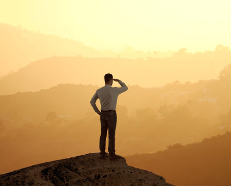 man in suit standing on rock and looking into the distance