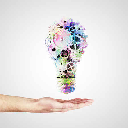 hand holding light bulb with color gears photo