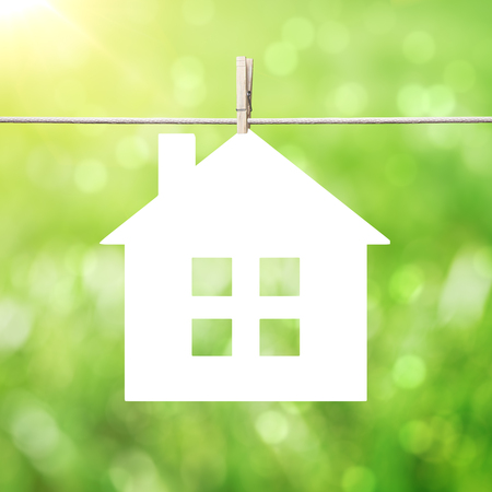 clench: paper house hanging on clothespins on abstract summer background