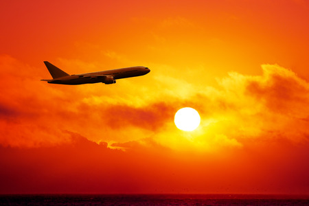 airplane in the sky at sunset Stock Photo
