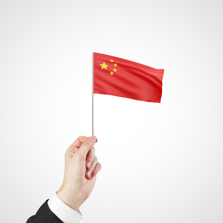 hand holding flag of China on gray background photo