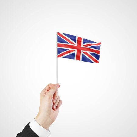 hand holding flag of United Kingdom on gray background photo