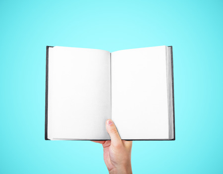 business book: hand holding a blank book on a blue background