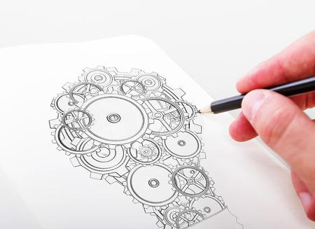 dibujo tecnico: mano drawning engranajes de la lámpara en un bloc de notas