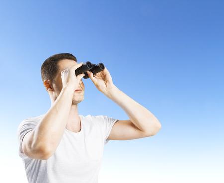 man looking through binoculars  on a blue background photo