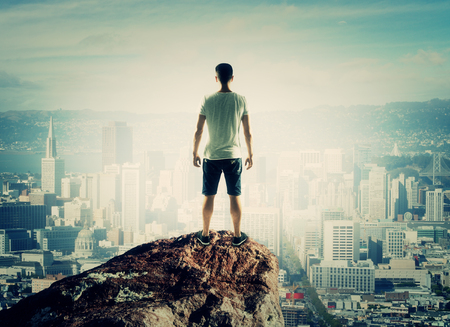 man stands on top mountain and looking to city photo
