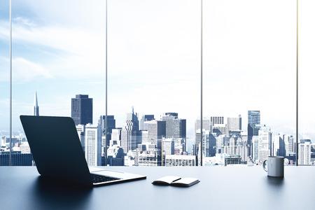 モダンなオフィスのラップトップとシティ ビュー