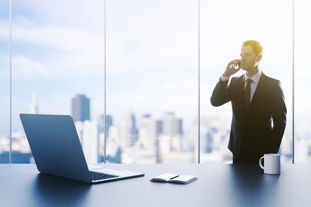 近代的なオフィスに立っているビジネスマンをクローズ アップ 写真素材