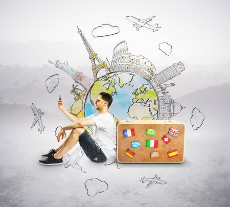 suitcase packing: men with cellphone sitting near travel suitcase Stock Photo