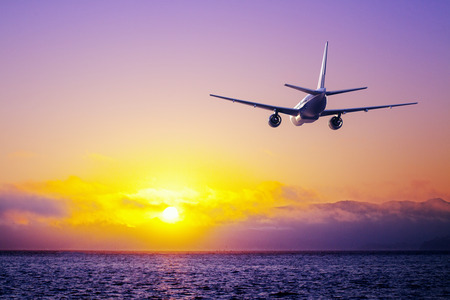 big airplane in the sky flying over ocean Stock Photo