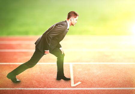 pista de atletismo: hombre de negocios de pie en la pista de atletismo para el atletismo