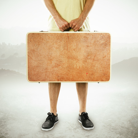 suitcase packing: man holding suitcase on a white background