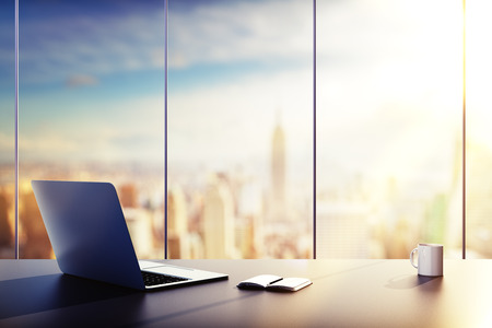 tabulka: laptop, pohár a deník na stole v kanceláři
