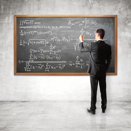 decides: businessman decides to financial equation on blackboard