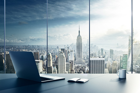 oficina: portátil, la taza y el diario sobre la mesa en la oficina
