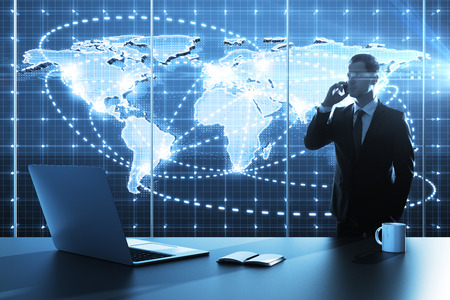 businessman standing in office with global business map Stock Photo