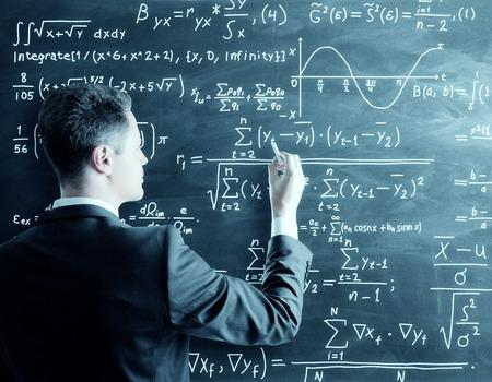 chalk writing: businessman writing formula on chalk board