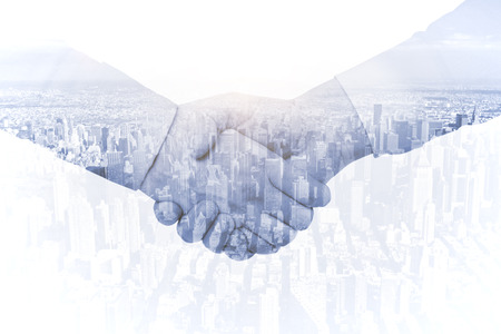 building trust: handshake on city background, double exposure