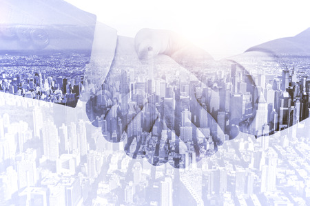 building trust: handshake on a city background, double exposure